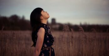 a-girl-standing-in-the-field-looking-up-the-sky-2
